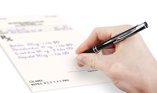 photo of a doctor's hand filling out a prescription
