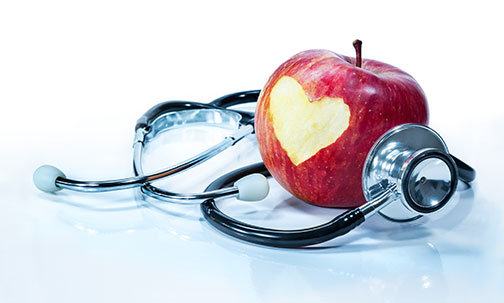 photo of a stethoscope and an apple with a heart carved out of it