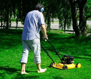 photo of man mowing his yard in bare feet
