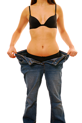 photo of girl showing weight loss in big jeans