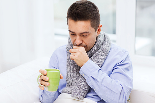 photo of ill man with flu drinking tea and coughing at home
