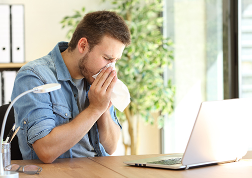 photo of guy sneezing in a wipe at office near a window
