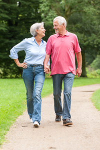 photo of active and happy senior couple walking in the park