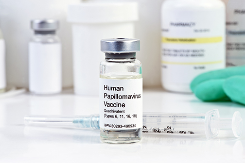 photo showing a vial of Human Papilloma Virus vaccine next to a syringe at a clinic